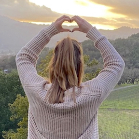 Girl raising hands to make a heart shade, reflecting the children we love